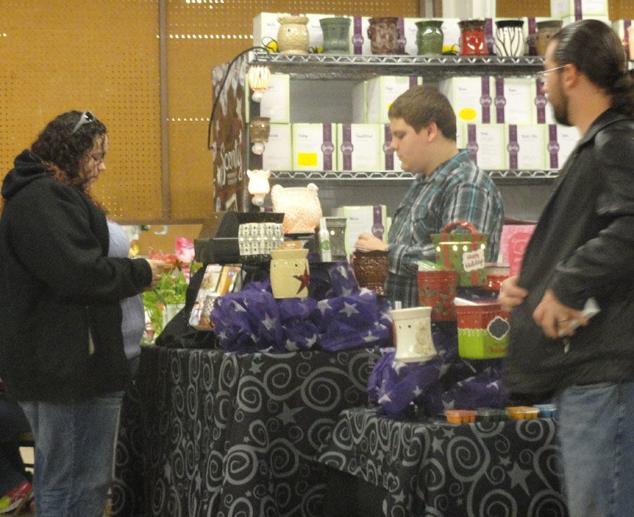 Vendor selling Scentsy items and people looking at items for sale
